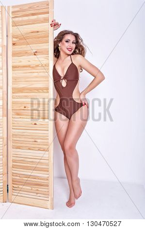 Slender attractive girl measures the swimsuit in a store. Shopping. Preparation for the beach season.