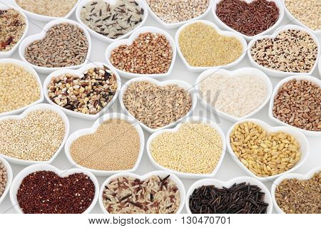 Healthy grain food in heart shaped bowls over white background.