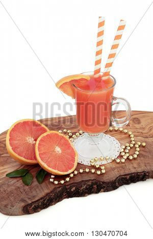 Ruby red grapefruit juice drink with fresh fruit, striped straws and gold bead decorations on an olive wood board over white background. High in vitamins, anthocyanins and antioxidants.