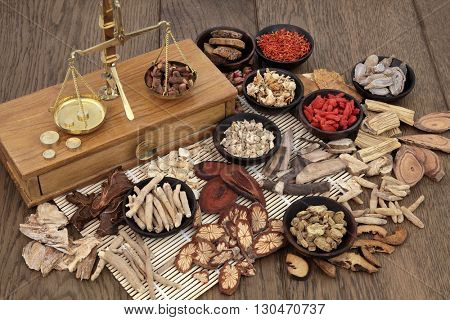 Traditional chinese herb ingredients used in alternative herbal medicine with old brass scales over bamboo and oak background.