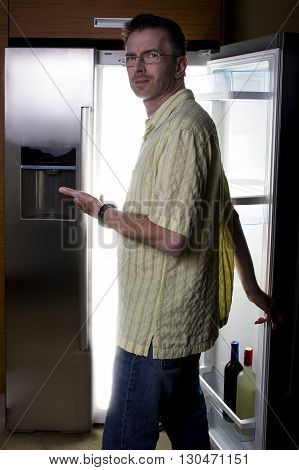 Man looking for food in an open fridge in a dark kitchen late at night