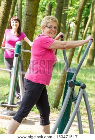 Elderly senior and young woman in sports wear exercising upper and lower body on outdoor gym in park trainer machine healthy sporty lifestyles and slimming concept