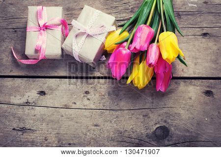 Bunch of bright yellow and pink spring tulips and boxes with presents on vintage wooden background. Selective focus. Place for text. Flat lay. Top view. Toned image.