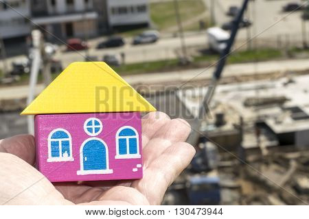 Wood house in hand on a background of construction