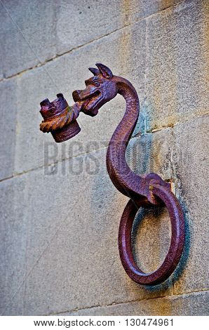 antique metal dragon is a bearer of a historic building