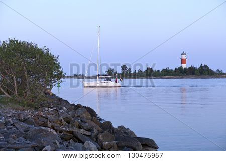BALTIC SEA, SWEDEN ON JUNE 02. View of a sailboat cross a strait on June 02, 2013 in Holmsund, Sweden. Lighthouses in the background, calm sea and evening. Editorial use.