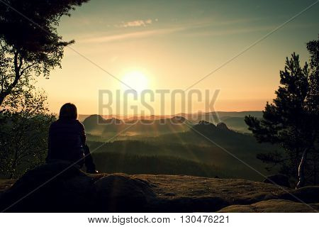 Young Woman hiker takes a rest on peak of the Mountain and enjoy daybreak