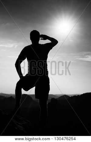 Hiker On Edge Of Sandstone Cliff In Rock Empires Park And Watching Over The Misty Valley To Sun. Bea