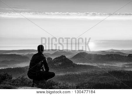 Sunrise Sports. Hiker In In Dark Sportwear In  Squatting Position On A Rock In Heather Bushes, Enjoy
