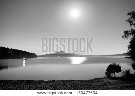 Romantic Full Moon Night At Lake, Calm Water Level With Moon Rays. Burh On The Hill.