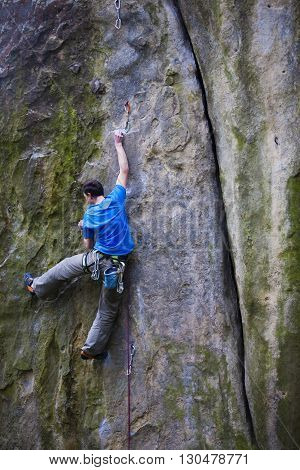 A Rock Climber Climbs Up The Mountain.