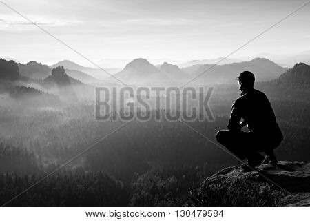 Runner in cap and in dark sportswear in squatting position on a rock enjoy the scenery