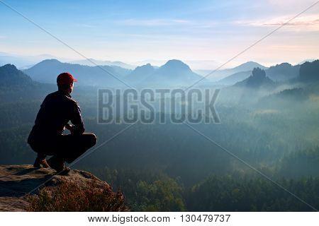 Runner In Red Cap And  In Dark Sportswear In Squatting Position  Enjoy Mountain Scenery