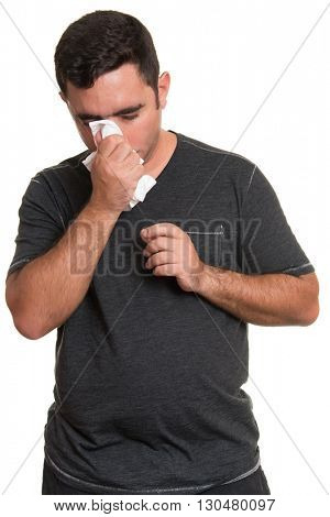 Portrait of a sick man with the flu, allergy, germs,cold, blowing his nose with tissue isolated on white background