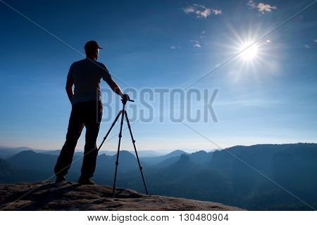 Professional photographer stay with tripod on cliff and thinking. Dreamy fogy landscape blue misty sunrise in a beautiful valley below
