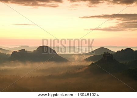 Tourist resort. Fantastic dreamy sunrise on the top of the rocky mountain with the view into misty valley