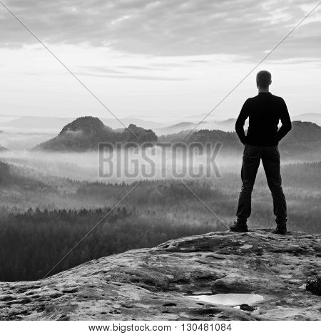 Alone Man Is Standing On Peak Of Sharp Cliff In Rock Empires Park And Watching Over The Misty And Fo
