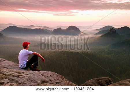 Adult Sportsman In White Shirt, Dark Trousars And Red Cap. Ginger Short Hair Man Sit On Sharp Cliff