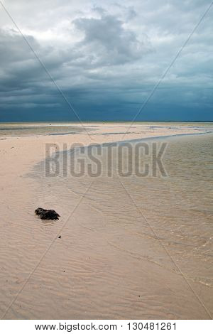 Isla Blanca Chacmuchuk Lagoon tidal beach under stormy skies at Cancun Mexico