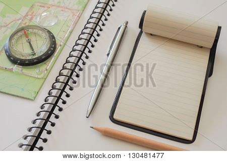 A small note pad on a larger spiral bound sketch pad with a silver cased pena plain lead pencil a map and a compass.