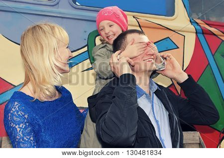 Father, mother and daughter making a joke or playing hide and seek