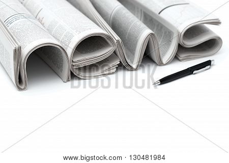 Stacks of modern newspapers composed in form of word NEWS on white background