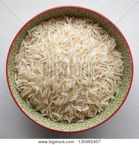 Uncooked long grain basmati rice in a colorful ceramic bowl.