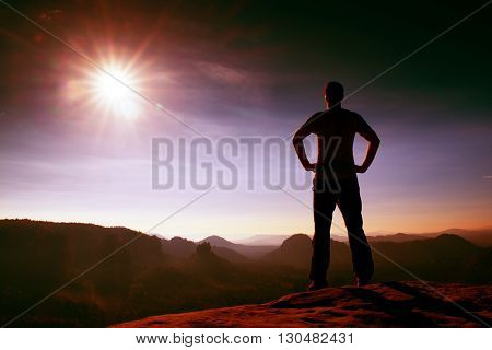 Happy man silhouette on sharp cliff of sandstone rock