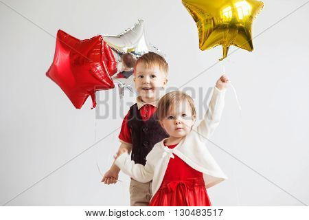 Little kids holding balloons in the form of stars. Children holding a star-shaped balloons. Happy children with colorful shiny foil balloons against a white background
