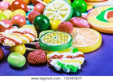 Colorful sweets and candies on a purple background. focus on the middle of the frame