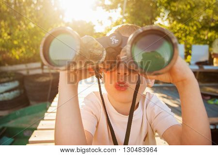 Little Boy Looking Through Binoculars On River Bank
