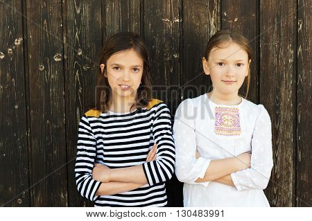 Outdoor fashion portrait of two cute girls of 7-8 years old, wearing dresses, standing against brown old wooden background