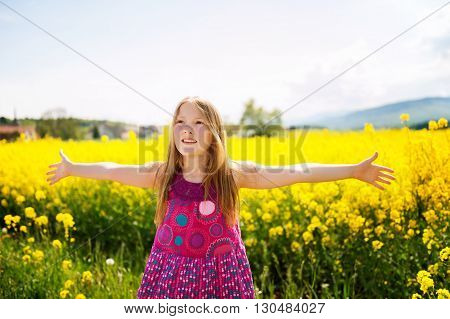 Outdoor portrait of a cute little girl playing with flowers in a countryside, arms wide open