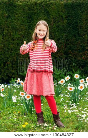 Cute little girl of 7-8 years old playing in the spring park between daffodils flowers, thumbs up, wearing stripe pullover, red skirt and tights