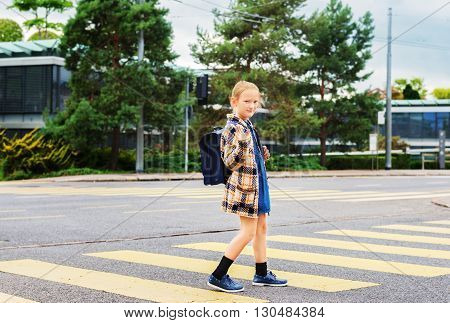 Pretty little schoolgirl with blue backpack crossing the road alone