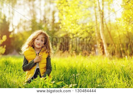 happy child girl in yellow vest walking in summer sunny forest. Kids exploring nature. Cozy rural scene