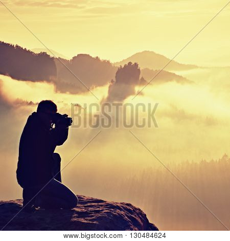 Happy Photo Enthusiast Is  Enjoying Fantastic Miracle Of Nature On Cliff On Rock. Dreamy Fogy Landsc