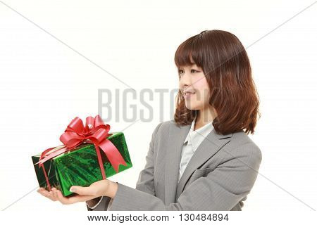 young Japanese businesswoman offering a gift on white background