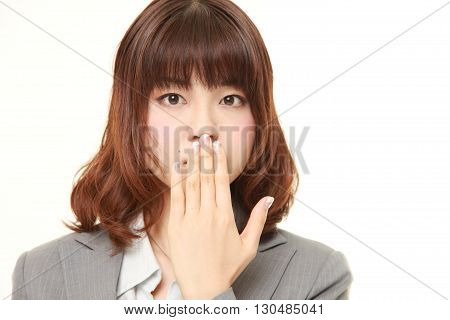 portrait of Japanese businesswoman making the speak no evil gesture on white background