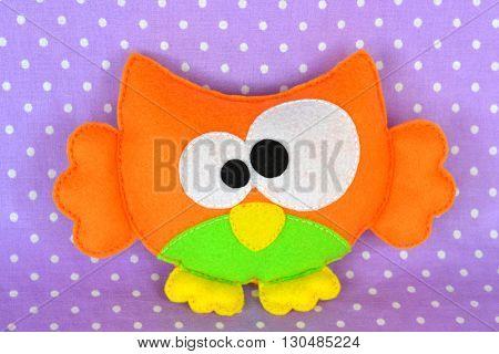 Funny felt owl toy isolated on purple fabric