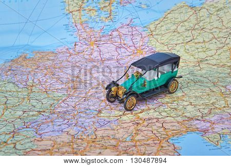 Small toy old car on road map. Image of travel concept.