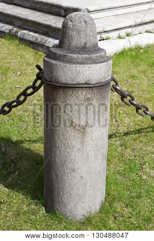 Element stone fence with iron chains. Architecture exterior