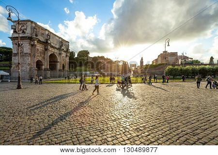 Rome, Italy - May 12, 2016: People and tourists walking in front of the Arch of Constantine spectacular at sunset, located between the Colosseum and the Arch of Titus on the Roman road.