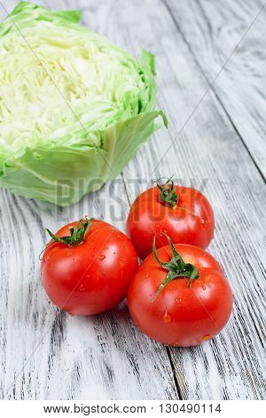 Cabbage and tomatoes on a wooden background