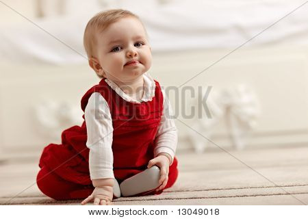 Little Girl Sitting On Carpet, Looking At Camera