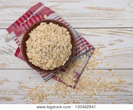 Oat flakes in ceramic bowl on white wooden background