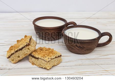 Two old ceramic cups of milk and two pieces of grated pie