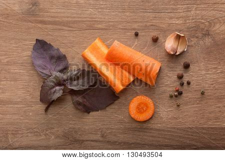 Top view of carrot purple basil cloves of garlic and black pepper on the wooden table