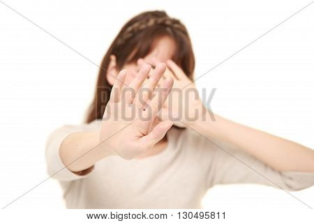 portrait of young woman making stop gesture on white background