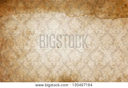 Dirty and spotted paper with vintage decorative ornament. Old wallpaper background.